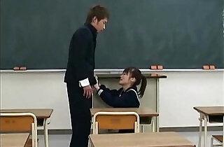 An Asian girl in a schoolgirls uniform is sitting in from.  xxx porn